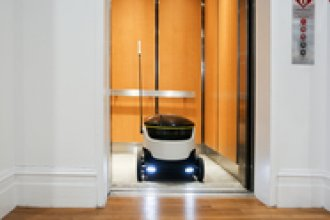 Starship Technologies' delivery robot exits the elevator in the company's office.