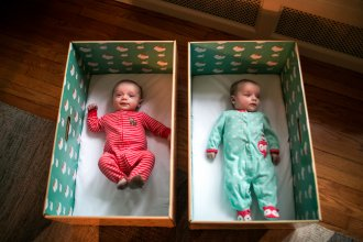 Twins Ryan and Nell Stimpert lie in their baby boxes at home in Cleveland. The cardboard boxes are safe and portable places for the babies to sleep.