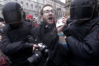 Riot policemen detain a journalist during a protest rally in St. Petersburg, on Sunday, where thousands crowded in for an unsanctioned protest against the Russian government.