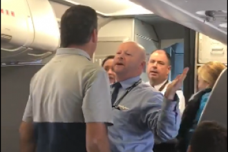 A passenger and an American Airlines employee stand face-to-face in a video captured by another passenger on an American Airlines flight, Friday.