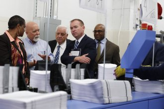 """White House Budget Director Mick Mulvaney (second from right) holds a copy of the president's 2018 budget at the Government Publishing Office's plant in Washington, D.C. Mulvaney describes the plan as """"taxpayer first."""""""