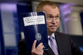 Budget Director Mick Mulvaney holds up a copy of President Donald Trump's proposed fiscal 2018 federal budget at the White House on Tuesday.