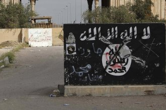 A defaced Islamic State flag is emblazoned on a wall in Tikrit, Iraq, in 2015. ISIS will generally claim responsibility for an attack within one day, though it can sometimes take longer.
