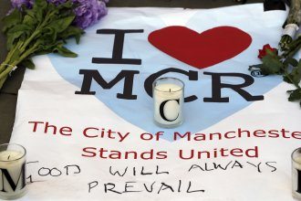 A sign with flowers and candles was placed on the ground after a vigil in Albert Square in Manchester, England, the day after the suicide attack at an Ariana Grande concert left 22 people dead Monday night.