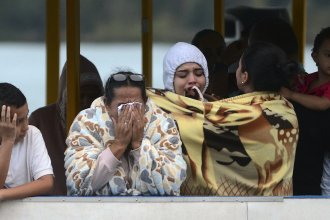 People who survived the capsizing of a ferry, cry as they wait for more information about their missing friends and relatives, at a reservoir in Guatape, Colombia, on Sunday.
