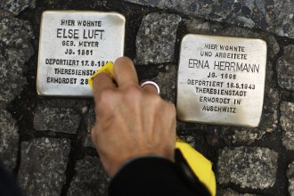 """A woman cleans a <em>Stolperstein</em>, or """"stumbling stone,"""" placed in the sidewalk in front of houses where victims of the Holocaust lived before they were deported and killed by the Nazis."""