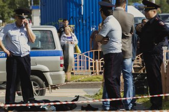 Police officers stand by the body of a man who was killed after an alleged stabbing attack on Saturday in the Siberian city of Surgut, Russia.