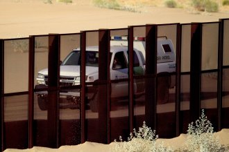 A U.S. Border Patrol vehicle drives along the U.S.-Mexico border fence near Yuma, Ariz., as seen from the outskirts of San Luis Rio Colorado, Mexico, in 2010. President Trump will visit the area on Tuesday.