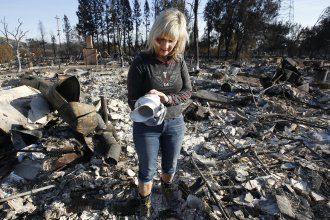 Debbie Wolfe looks at the antique pitcher that once belonged to her grandmother after finding it in the burned ruins of her home on Tuesday in Santa Rosa, Calif.