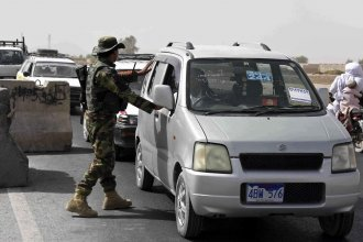 An Afghan National Army soldier searches a vehicle at a checkpoint in Kandahar, Afghanistan, Thursday on the way to the Maiwand army base, the site of the Taliban attack late Wednesday.