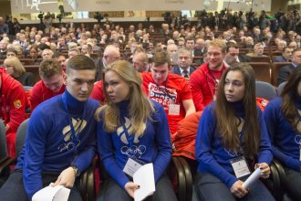 """Russian short track athletes, first row, and ice hockey players wearing sweatshirts with the words """"Russia is in my heart"""" attend a Russian Olympic Committee meeting  Tuesday. The Russian committee said it will support athletes who compete at the 2018 Winter Games despite a ban on the national team."""