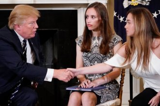 President Trump shakes hands with Marjory Stoneman Douglas High School student Ariana Klein as fellow Stoneman Douglas student Carson Abt watches at the start of a listening session on school safety with teachers and students at the White House Wednesday.
