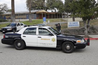 LA County Sheriff's patrol cars leave El Camino High School in Whittier, Calif., on Wednesday. A 17-year-old student threatened to open fire at the school days after the massacre at a Florida school. An alert security guard who overheard him reported it to police, who went to the boy's home and found two AR-15 rifles, authorities said Wednesday.
