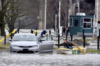 """Mathias """"Dale"""" Dekker (right) piloted his boat to rescue John Parker when the Red Cedar River flooded near Michigan State University in East Lansing, Mich., on Wednesday."""