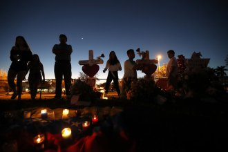 People visit a makeshift memorial outside Marjory Stoneman Douglas High School, where 17 students and faculty were killed in a mass shooting in Parkland, Fla.