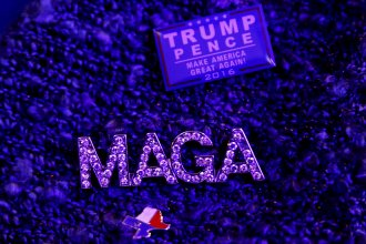 """A CPAC attendee wears a """"Make America Great Again,"""" Trump-Pence and Texas flag pins at the annual conservative conference at National Harbor, Md., on Thursday."""