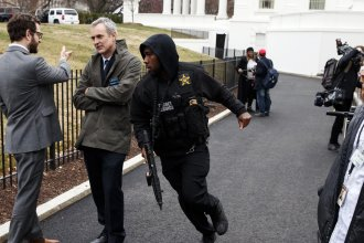 A Secret Service officer hurries past reporters after a vehicle struck a security barrier near the White House Friday.