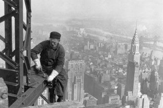 A worker bolts beams during construction of the Empire State Building in 1929; the Chrysler Building can be seen in the background. (Photo via Wikimedia)