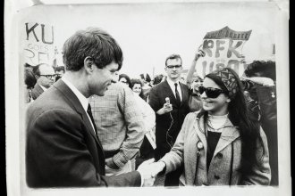 Robert F. Kennedy shakes a woman's hand while visiting the University of Kansas in 1968.  (Photo from University Archives, Spencer Research Library, University of Kansas)