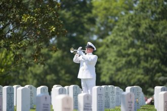 A bugler from the U.S. Navy Band plays taps during a graveside service in Arlington National Cemetery. (U.S. Army photo by Elizabeth Fraser)