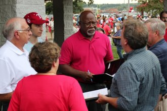 Rep. Willie Dove (center, in red) talking with Rep. Jim Karelskint (left, in white) and other organizers of a public meeting about the Tyson project last year. (Photo by Stephen Koranda)