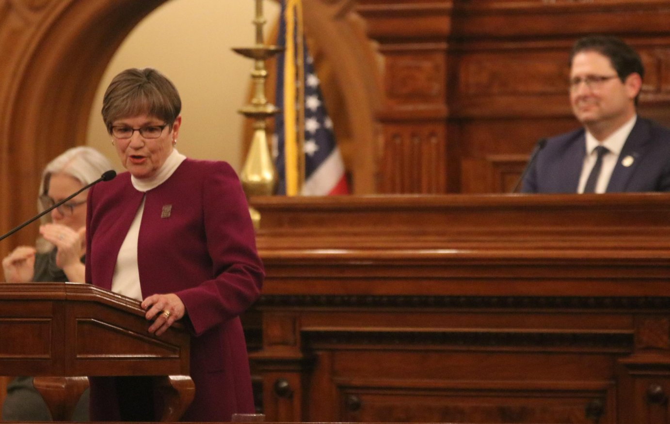 Gov. Kelly speaks at the State of the State address while House Speaker Ron Ryckman watches. (Photo by Daniel Caudill)