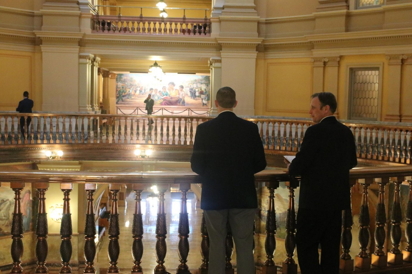 A limited number of people were allowed in the Statehouse this week to slow the spread of the coronavirus, but staffers, lobbyists and lawmakers still found time to chat at the rail. (Photo by Daniel Caudill, Kansas News Service)