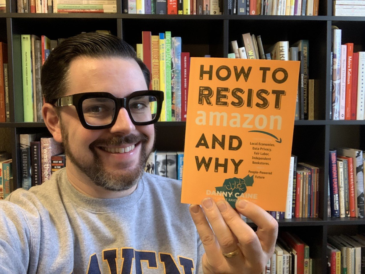 Picture description is Danny Caine holding up book, standing in front of bookshelves
