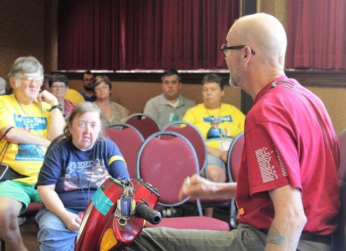 Mike Oxford, director of the Topeka Independent Living Resource Center, speaks to disability advocates in Topeka after returning from Washington, D.C., where he was arrested during a protest of the new Senate health bill. (Photo: Jim McLean, Kansas News Service)