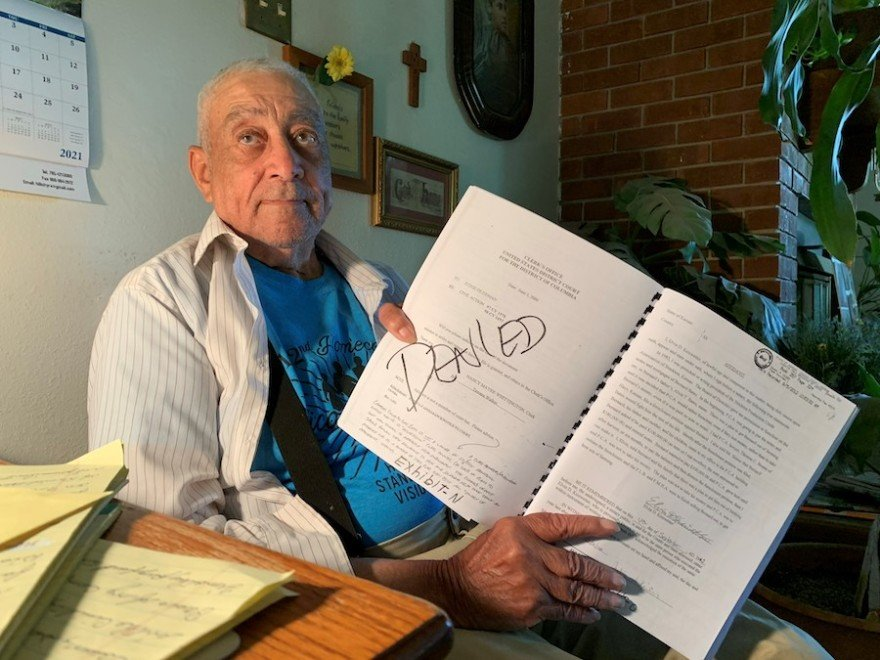 Bernard Bates holds a notebook of documents from the lawsuits he's been a part of while trying to get his farmland back. (Photo by David Condos, Kansas News Service)