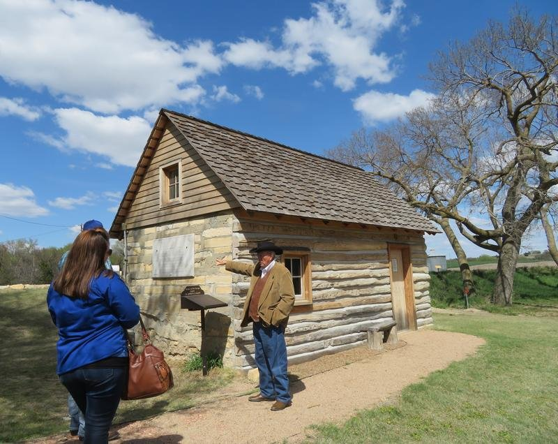 El Dean Holthus, of Smith Center, leads a tour of the property where Dr. Brewster Higley wrote 'Home on the Range,' including a restored cabin where Higley lived.