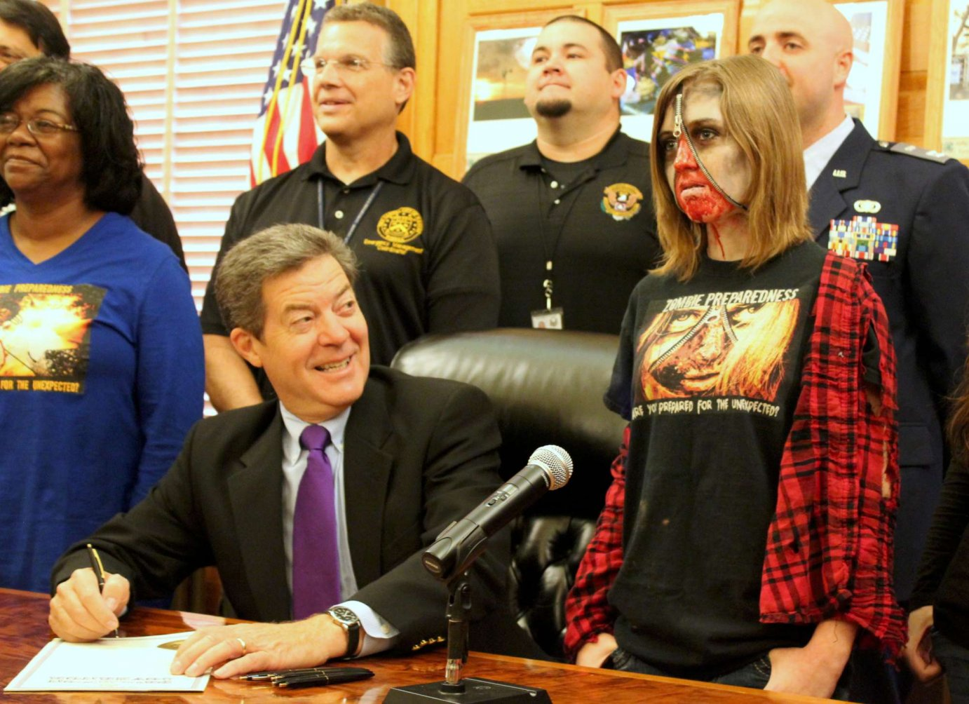 Governor Brownback and 15-year-old Faith Tucking at the signing ceremony. (Photo by Stephen Koranda)