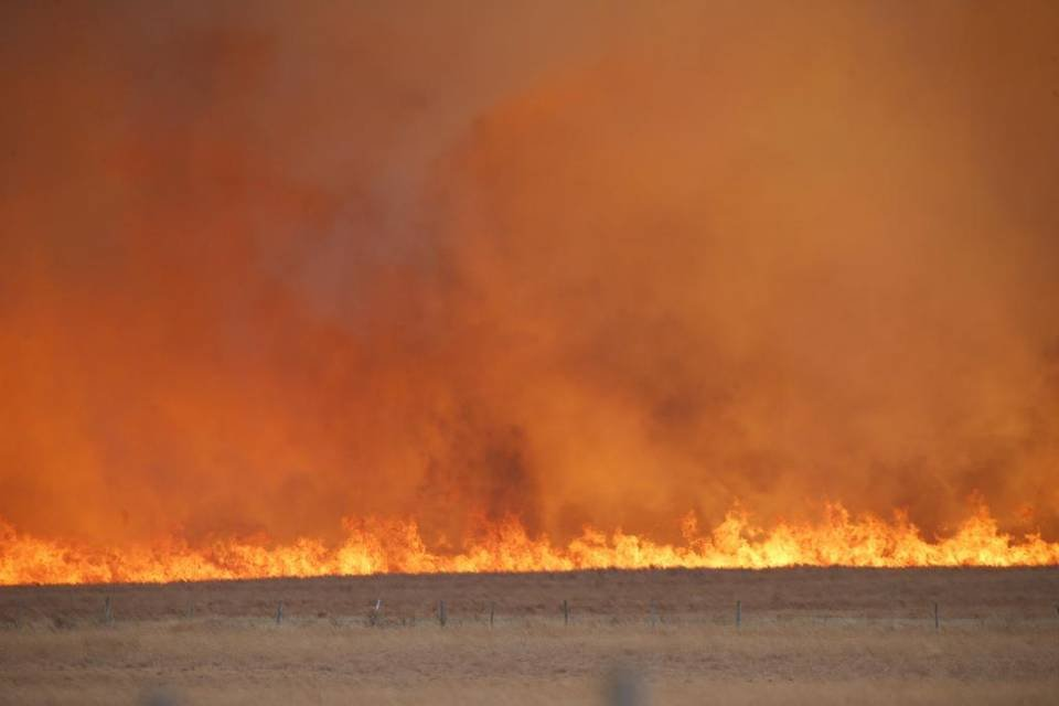 Driven by 30 MPH winds, a prairie fire jumps a road in Comanche County, near the Kiowa County line, on March 7, 2017.  (Photo by Bo Rader, The Wichita Eagle)