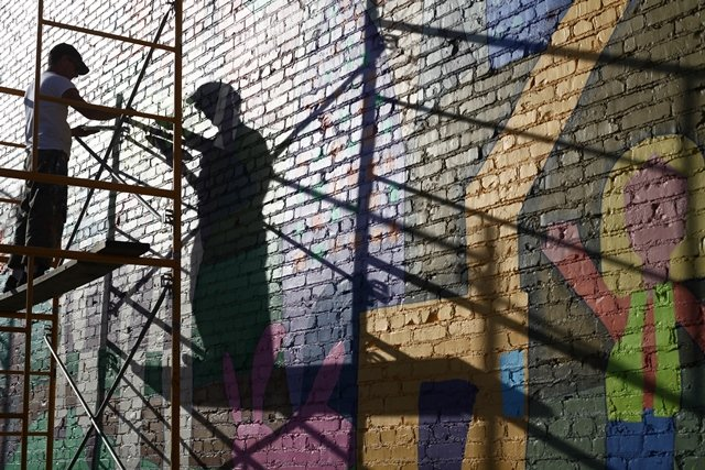 "Muralist Dave Loewenstein at work (Photo taken from the documentary film ""Called to Walls,"" used with permission of Queen Alidore Films)"