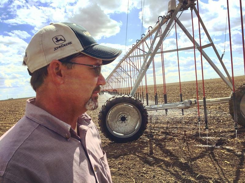 Farmer Clay Scott stands in front of one of his center-pivot irrigation systems in southwest Kansas.  (Photo from HPPR)