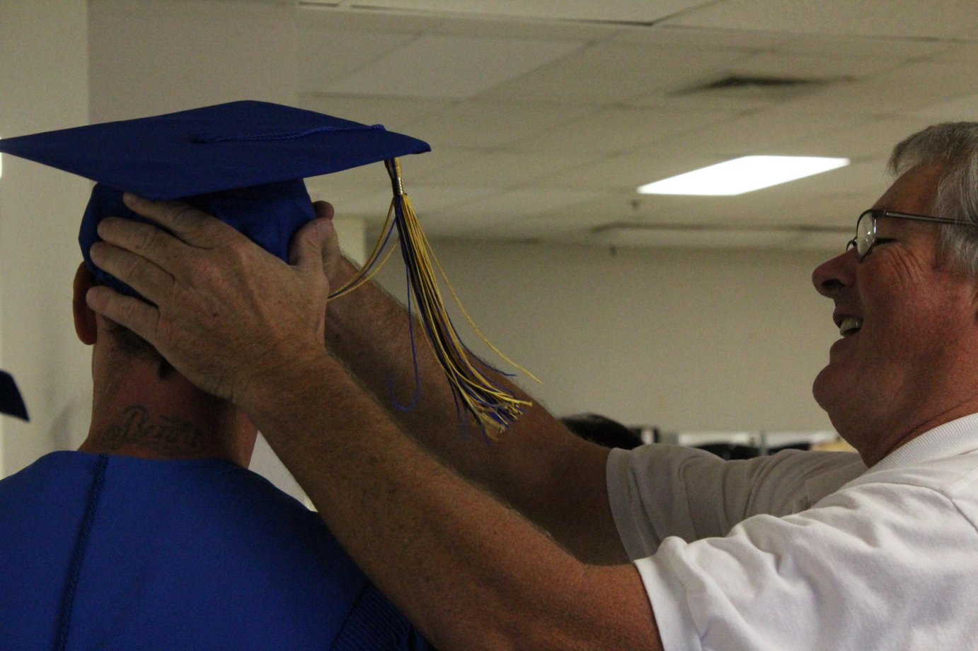 Each graduate briefly wore a mortar board with a tassel so they could be photographed at the ceremony. The inmates will be given a copy of their photo to send home and another to keep in their possession. (Credit Nadya Faulx)