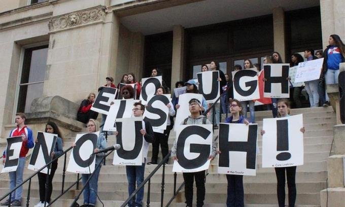 """Students spell out """"enough is enough"""" on the steps of the old courthouse in downtown Wichita. Each sign bore the name of a person killed in last month's school shooting in Parkland, Florida. (Photo Credit: Nadya Faulx, KMUW Radio)"""