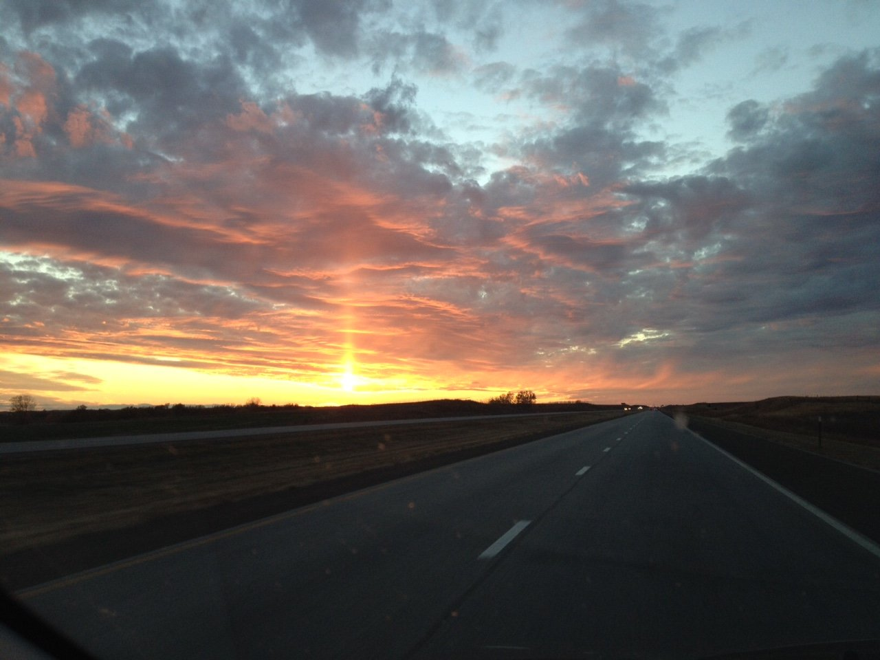 The sun sets along this stretch of Kansas highway. (Photo be J. Schafer)