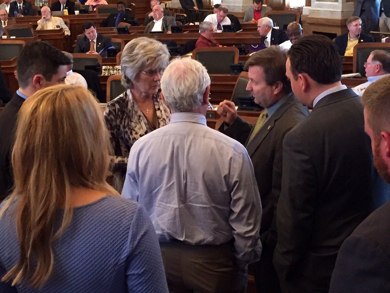 Lawmakers confer on the House floor Tuesday. (Photo by Stephen Koranda)