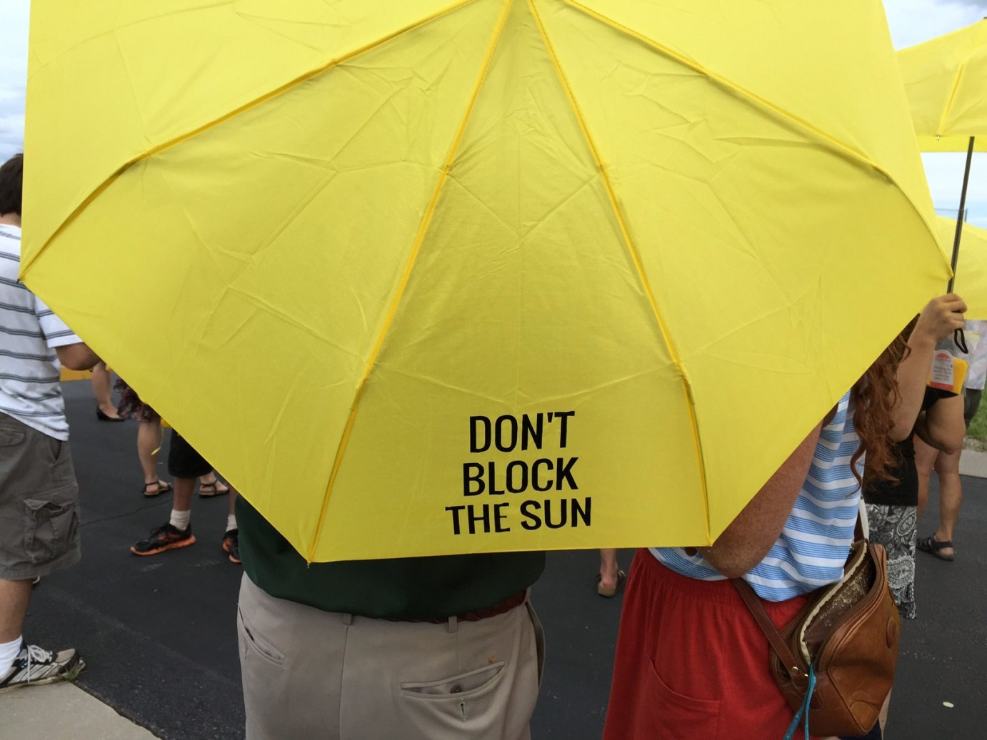 Opponents of Westar's plan carry yellow umbrellas to show their support for solar energy. (Photo by Stephen Koranda)