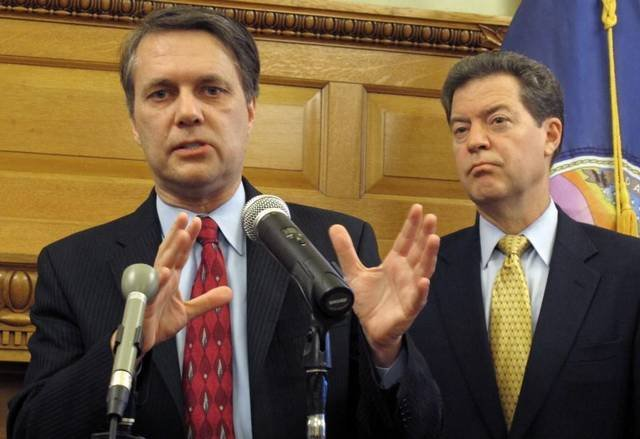 Lt. Governor Jeff Colyer (left) has hired the director of the Kansas Republican Party to serve as a special assistant as he prepares to take over for Governor Sam Brownback (right).  (Photo credit AP)