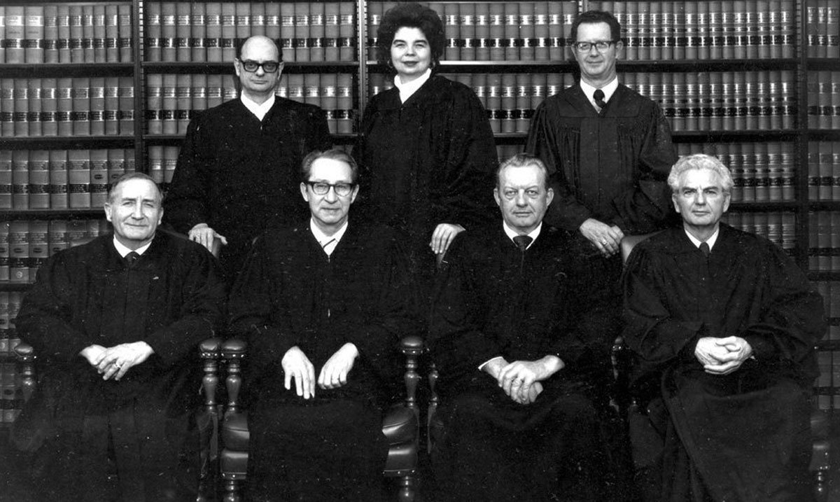 An official photograph of the Kansas Supreme Court Justices in 1978. The justices are identified as: (seated) David Prager, Alex M. Fromme, Alfred G. Schroeder, and Perry L. Owsley, (standing) Richard Winn Holmes, Kay McFarland, the first woman to be appointed to the high court, and Robert H. Miller. (Photo Courtesy of Kansas Historical Society / kansasmemory.org)