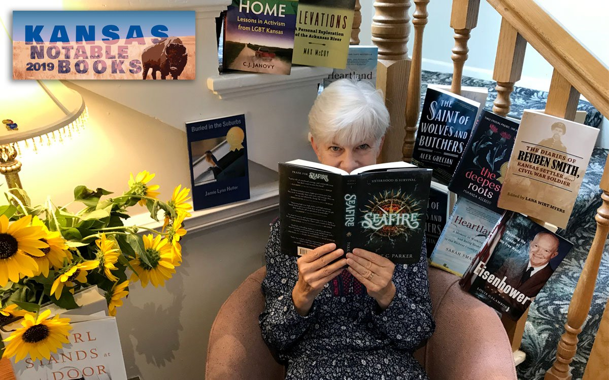 Kaye McIntyre holding book, surrounded by books