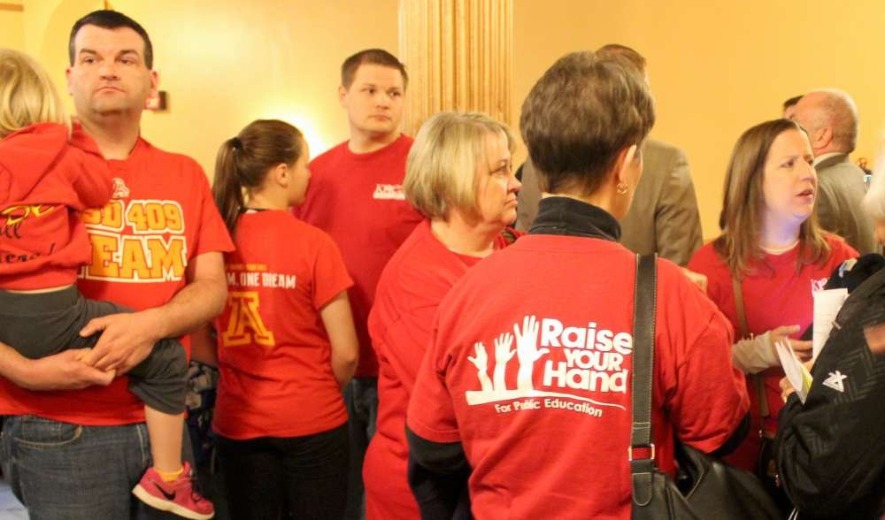 Educators wearing red shirts gathered to protest the bill. (Photo by Stephen Koranda)