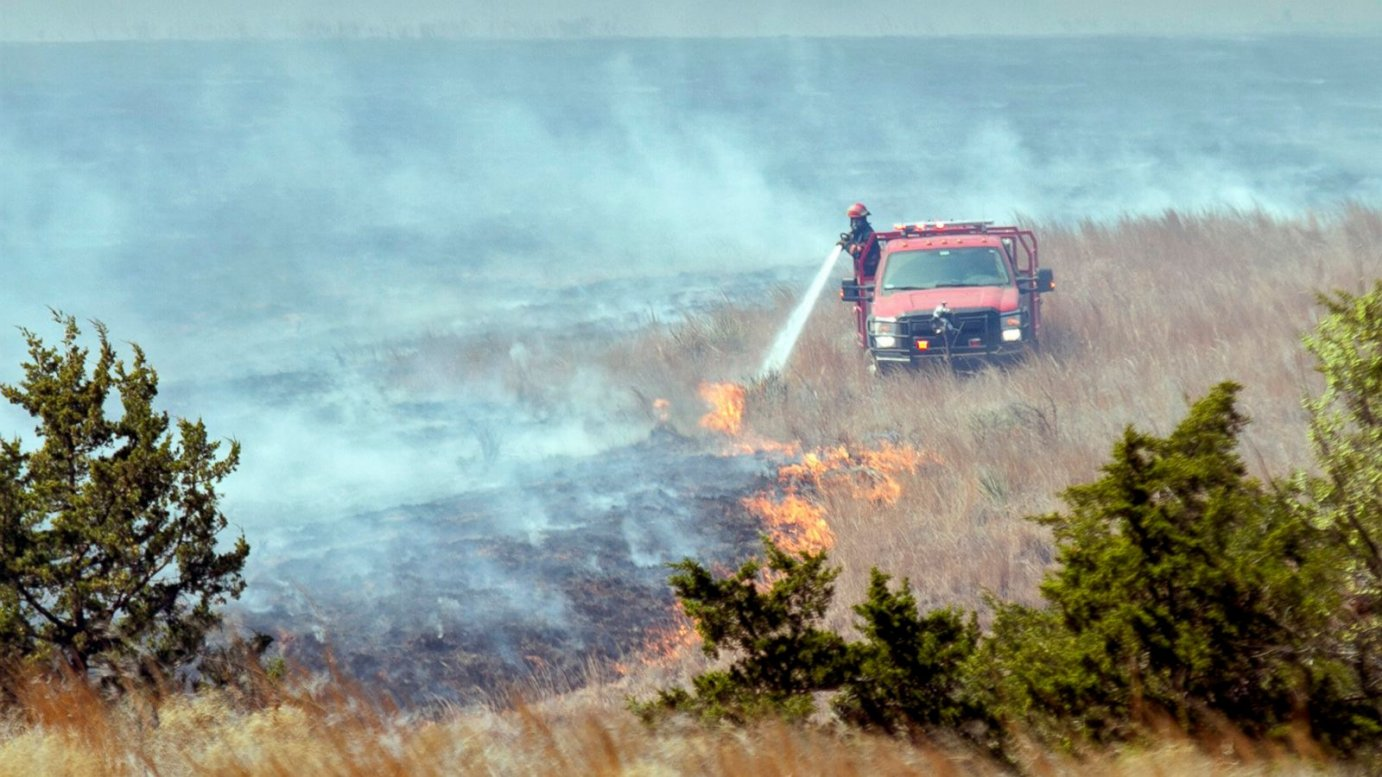 A firefighter crew douses a line of grass fire about 15 miles southwest of Medicine Lodge on Thursday, March 24, 2016.  More than 200 firefighters are battling an active fire line stretching 30 to 40 miles long in Barber County.  (Mike Hutmacher/The Wichita Eagle via AP)
