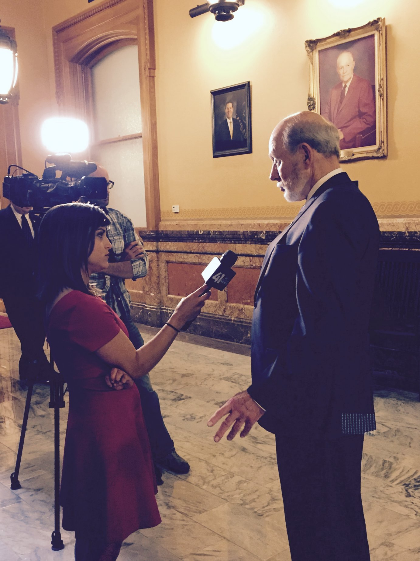 State Senator Les Donovan, chairman of the Senate Tax Committee, interviewed by a TV reporter.  (Photo by Jim McLean, KHI News Service)