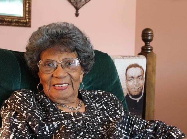 Leola Montgomery Brown sits in her living room in Topeka next to a blanket depicting the Brown v. Board of Education decision.  Her husband, Oliver Brown, seen behind her, was the lead plaintiff in the case. (Photo by Carla Eckels, KMUW Radio)