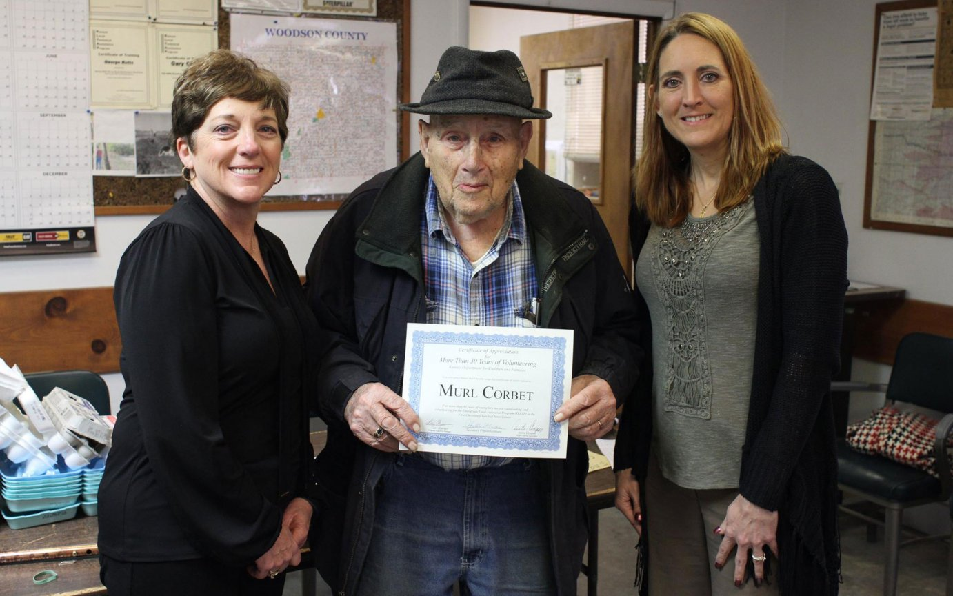 After 30 years of service, 96-year-old Murl Corbet is retiring from his work as a food distribution volunteer in Yates Center, Kansas.  Corbet is pictured with TEFAP East Region Community Relations Director Anita Cooper (left) and Economic and Employment Services Food Distribution Unit Manager Lori Slusser (right).  The Kansas Department for Children and Families facilitates food distribution that help nearly 154,000 low-income Kansans each year through TEFAP.  (Photo courtesy of KDCF)