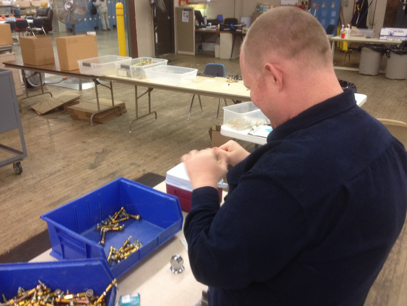 A client of the Occupational Center of Central Kansas assembles steering parts for riding lawnmowers in this sheltered workshop.  (Photo by Bryan Thompson)