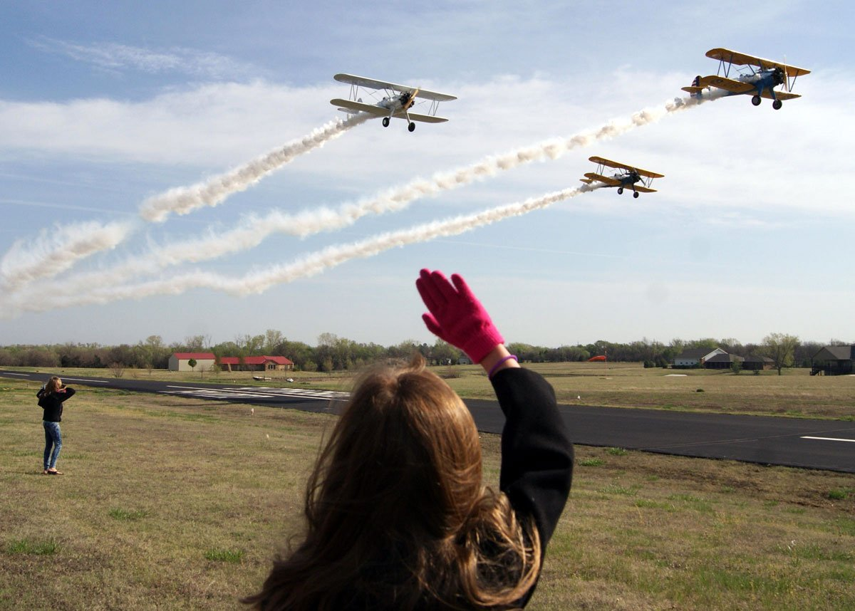 One of the girls from the book club waves as three pilots in Boeing Stearman biplanes fly over the airfield. The planes are from Benton, Kan., and did several passes by the hangar for the girls. (Photo by Abigail Wilson/KMUW)